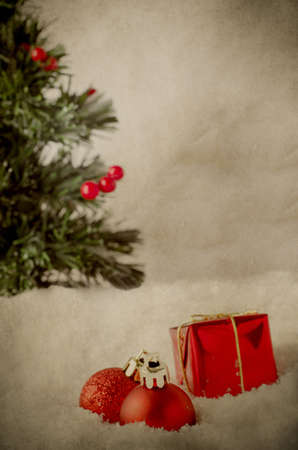 fake christmas tree: Red Christmas ornaments nestled in fake snow with Christmas tree in background laden with berries.  Grungy vintage appearance.