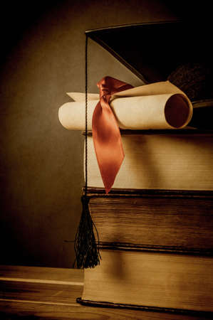 A stack of old books, topped with a mortarboard and  diploma scroll, tied with red ribbon.  Aged and vignetted for vintage effect.  Blackboard in background provides copy space to left. Stock Photo