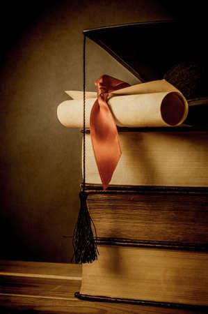 Une pile de vieux livres, surmonté d'une toque et un diplôme défilement, à égalité avec ruban rouge. Vieilli et en dégradé pour un effet vintage. Blackboard en arrière-plan fournit copie espace à gauche.
