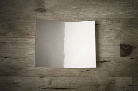 Overhead shot of a blank greeting card, lying face upwards and opened on a wooden planked table Foto de archivo