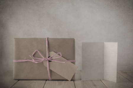 cutting costs: Photograph with vintage treatment of a gift box wrapped in brown paper, tied to a bow with with pale pink raffia and with blank parcel tag label facing front