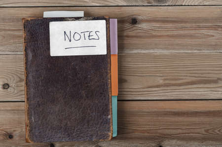 Overhead shot of an old, weathered brown notebook updated with colourful new tab dividers along side and bookmark poking out from top Stok Fotoğraf
