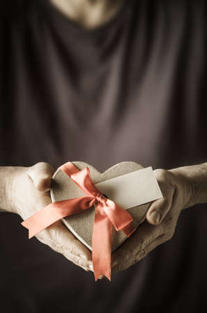 Male hands holding out a heart shaped gift box, tied to a bow with satin ribbon.  A blank gift label faces front to provide copy space for message.  Mans body provides soft focus background.  Low saturation for retro feel. photo