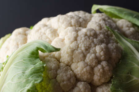 head of cauliflower: Close up (macro) of a head of leafy white cauliflower against a black background. Stock Photo
