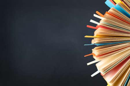 directorio telefonico: Un �ndice de la tarjeta de rotaci�n, lleno de tarjetas y dividido con fichas multicolores. recortada en lado derecho del marco. Un fondo de pizarra negro proporciona espacio de copia a la izquierda. Foto de archivo
