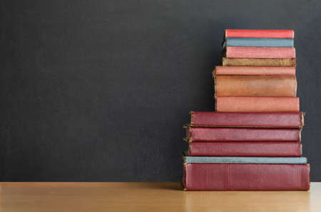 tatty: A pile of old, shabby, well used text books stacked in a pile on a wooden desk in front of a black chalkboard.  Copy space on left side. Stock Photo