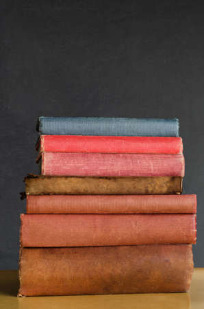 spines: Close shot of a pile of old, shabby, well used text books stacked in a pile on a desk in front of a black chalkboard.  Copy space above.