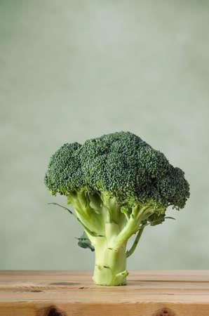 brocoli: Toda una cabeza de brócoli crudo en una mesa de tablones de madera, de pie en el vástago contra un fondo verde con espacio de copia anterior.
