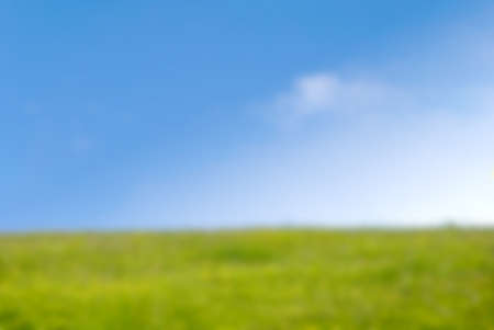 out of focus: Background blur photograph of grassy hill in Springtime on a bright sunny day with blue sky and fluffy white clouds.