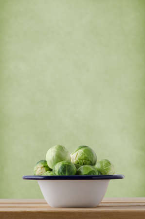 cruciferous: Brussel sprouts, piled into an enamel cooking tin, on wood planked kitchen table against pale green textured wall with copy space above. Stock Photo