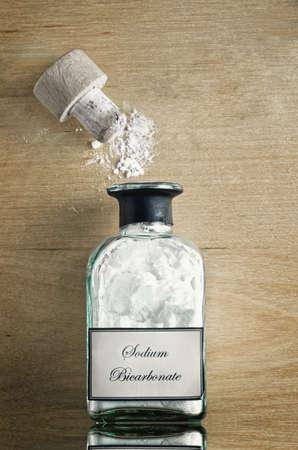 non toxic: Una botella de estilo vintage de bicarbonato de sodio (bicarbonato de sodio) en la brillante superficie de madera reflexivo. Cork abierto y el polvo se dispersaron. Foto de archivo