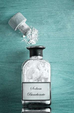 Ein Vintage-Stil Flasche Natriumbicarbonat (Backpulver) auf glänzenden reflektierende Cyan oder türkisblauen Holzoberfläche. Cork offen und Pulver verstreut. Standard-Bild - 39057203