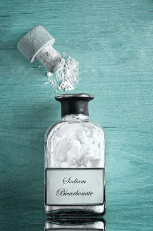 A vintage style bottle of Sodium Bicarbonate (baking soda) on shiny reflective cyan or turquoise blue wooden surface.  Cork open and powder scattered.