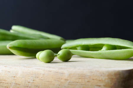 intact: Close up (macro) of three peas with stalks intact on wooden chopping board. Stock Photo