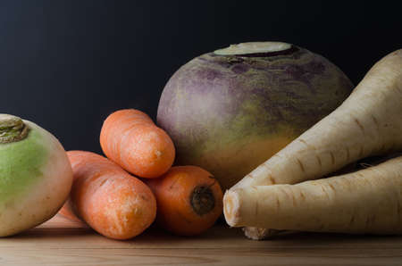 unwashed: Close cropped shot of still life arrangement.  Raw, unwashed root vegetables on a wood plank table with a black chalkboard background.  Includes turnip, carrots, swede and parsnips. Stock Photo