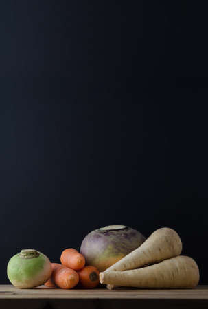 swede: Still life arrangement of root vegetables (turnip, carrots, swede and parsnips) on a wood planked table with a chalkboard in soft focus background for copy space.