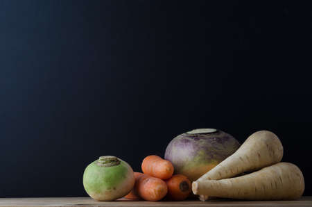 swede: Still life arrangement of root vegetables (turnip, carrots, swede and parsnips) on a wood planked table with a blackboard in soft focus background for copy space. Stock Photo