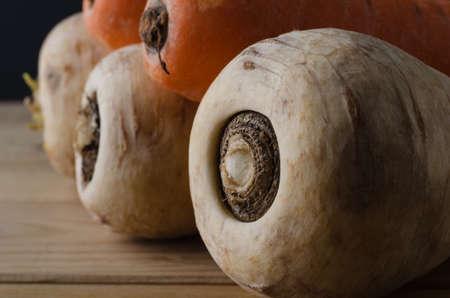 unwashed: Ortaggi a radice. Primo colpo di una fila di pastinache con carote lavate accumulata in cima, che si allontana per lo sfondo sul tavolo in legno da cucina dogato.