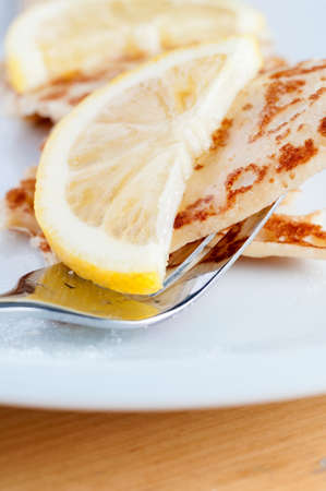 caster: An English style pancake, topped with half a lemon slice and sprinkled with caster sugar, being lifted from white plate by shiny fork.