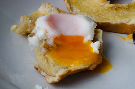 seeping: Close up of a partly eaten free range fried egg on toasted bagel with yolk seeping over the edge.  Remaining half bagel in background. Stock Photo