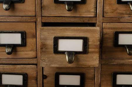 biblioteca: Un viejo gabinete de madera estilo de biblioteca cajones índice tarjeta con los titulares de etiquetas y etiquetas en blanco que enfrentan frontal. Un cajón en el medio se abre. Foto de archivo