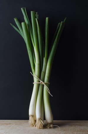 spring onions: A bunch of spring onions (scallions) tied with string and standing upright on a scratched and worn wooden surface against a black chalkboard background.