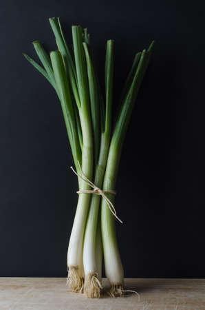 cebolla: Un manojo de cebolletas (cebolletas) atados con una cuerda y de pie en posición vertical sobre una superficie de madera rasguñado y desgastado contra un fondo negro pizarra.