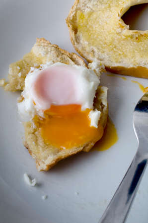 A partly eaten free range fried egg with yolk spilling onto bagel and plate below.  Fork visible.  Shot from diners perspective.