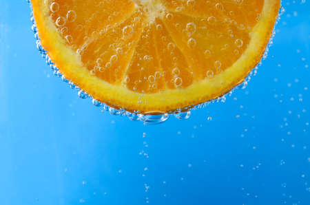 oxygenated: Close up of a fresh orange slice at top of image and facing forwards, suspended in sparkling bright blue water.  Oxygen bubbles float upwards and cover the front and edges of the fruit. Stock Photo