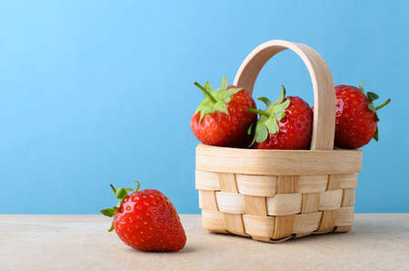 overfilled: Fresh red strawberries. piled up high and filling a small woven basket on a wooden surface against light blue background.