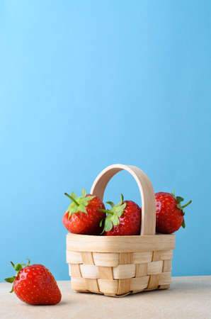 piled: Fresh red strawberries, piled high to fill a small woven basket on a wooden surface against light blue background. Stock Photo