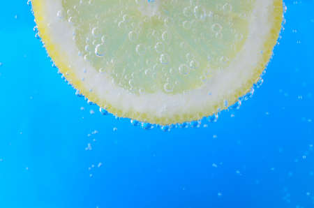 oxygenated: Close up of a freshly cut lemon slice at top of image and facing forwards, suspended in sparkling bright blue water.  Oxygen bubbles float upwards and cover the front and edges of the fruit. Stock Photo