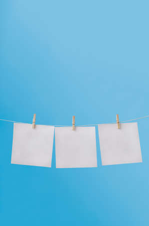 notices: Vertical image of three squares of note paper for messages, pegged to hang on washing line against a blue sky.  Left blank to provide copy space for notices.