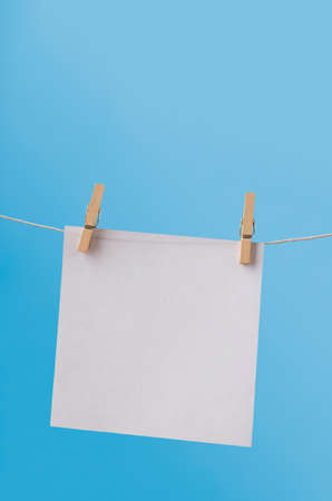 one sheet: One, single sheet of white, square paper, hanging from a clothes line on wooden pegs against a clear blue sky.  Left blank for copy space. Stock Photo