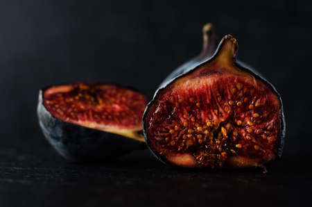 innards: Close up of well ripened figs, cut open to expose seeds and juicy innards.  Still life composition on black slate with black background.