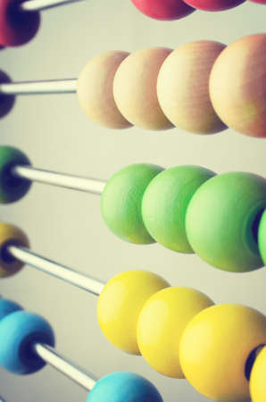 cross processed: Close up of rows of abacus beads in bright colours,  angled and leading away into soft focus. Cross processed to create retro effect.