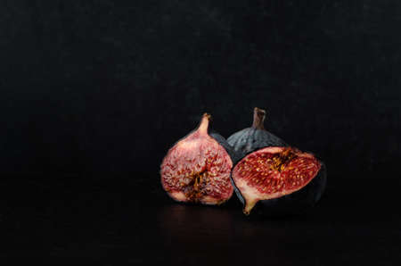 overly: A still life arrangement of very ripe and juicy figs in a three piece grouping on black slate against a chalkboard background. Stock Photo
