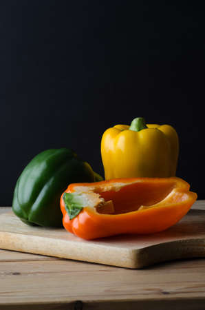 bell peppers: A still life arrangement of three bell peppers (green, yellow and orange) on a wooden chopping board, with planked kitchen table below and black background.  Moody lighting.