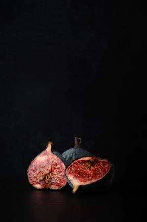 overly: A still life composition of very ripe and juicy figs in a three piece grouping on black slate against a chalkboard background.  Copy space above. Stock Photo