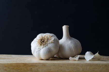 Still life arrangement of two whole, unpeeled garlic bulb heads, with some loose papery skin scattered on wooden chopping board with black background.