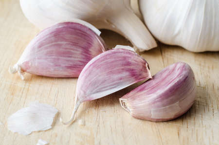 papery: Close up view of  three pink garlic cloves, with whole unpeeled bulbs in background.  Papery peelings are scattered on a scratched wooden chopping  board.