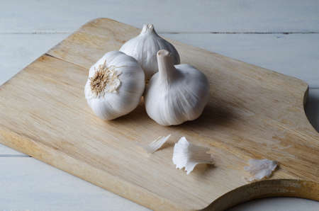 elevated view: Angled elevated view of three garlic bulbs grouped on an old wooden chopping board with white painted wood plank kitchen table underneath.  Flakes of garlic paper scattered on board. Stock Photo