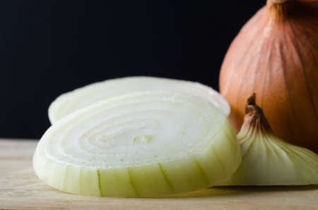 cures: Close up of onion slices on wooden chopping board with whole, unpeeled onion behind and black background.