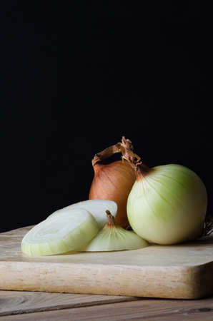 unpeeled: Still life arrangement of onions, whole, sliced, peeled and unpeeled on a wooden kitchen chopping board against a black background. Stock Photo