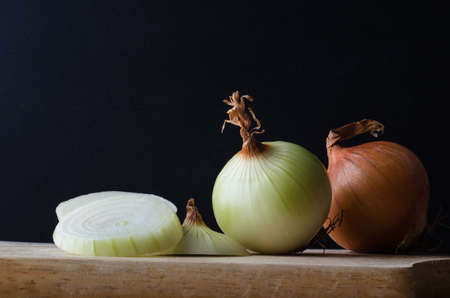 onion: Still life arrangement of onions, whole, sliced, peeled and unpeeled on a wooden kitchen chopping board against a black background. Stock Photo
