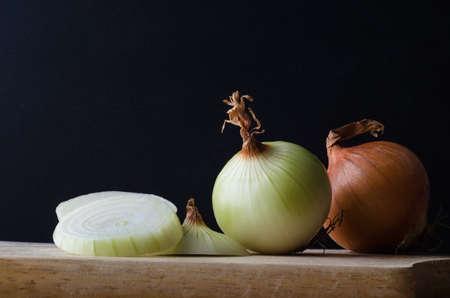 cebolla: Todavía arreglo de la vida de cebollas, entero, en rodajas, pelado y sin pelar en una tabla de cocina de madera de cortar sobre un fondo negro. Foto de archivo