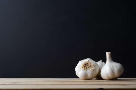 garlic: Tres cabezas de ajo enteras agrupadas en una disposición de naturaleza muerta en la madera tablones mesa de la cocina con el fondo negro pizarra proporcionar copia espacio.