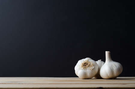 Three whole garlic bulbs grouped in a still life arrangement on wood planked kitchen table with black chalkboard background providing copy space.
