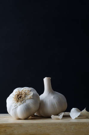 unpeeled: Still life arrangement of two whole, unpeeled garlic bulb heads, with some loose papery skin scattered on wooden chopping board with black background.