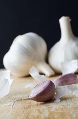 ajo: Dos cabezas de ajo enteras en el fondo, con dientes de color rosa en primer plano en una tabla de cortar de madera rodeadas de fragmentos dispersos de peelings papel shedded cerca la imagen (macro). Foto de archivo